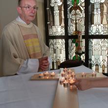 Pfarrer Franz-Josef Schubert während eines Auferstehungsamtes. Für die Verstorbenen werden Teelichter entzündet.